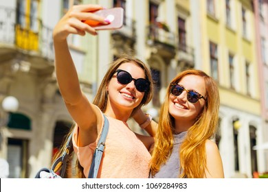 happy girlfriends make a selfie on the background of the city on a sunny day