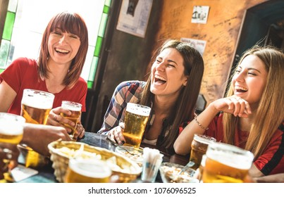 Happy girlfriends women group drinking beer at brewery bar restaurant - Friendship concept with young female friends enjoying time and having genuine fun at cool vintage pub - Focus on left girl