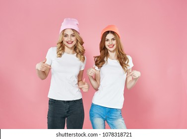 happy girlfriends women in white T-shirts, caps, studio, emotions, logo