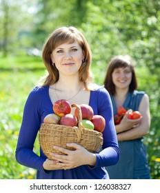 Happy girls with apples harvest in garden