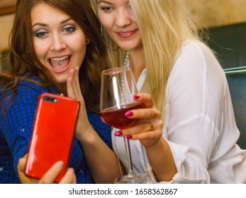 Happy girls best friends drinking alcohol in night club, gossiping, talking and taking self photo with phone
