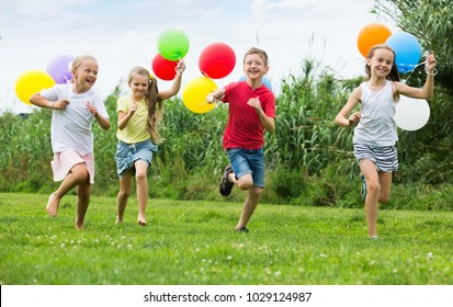 Happy girls and boy running all together  with multicolored balloons in backyard