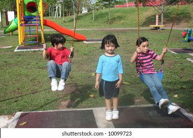 Happy girls and boy swinging in the park