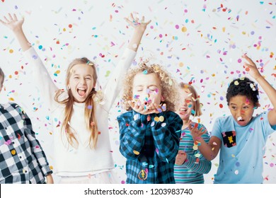 Happy girls and boys having fun together during birthday party with confetti