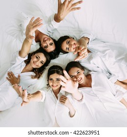 Happy girls with a bride on the white bed
