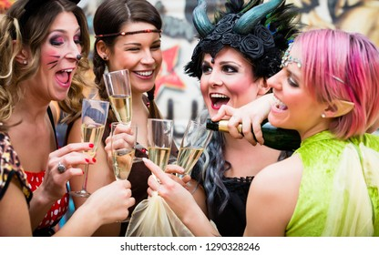 Happy girls at Carnival parade clinking glasses with champagne
