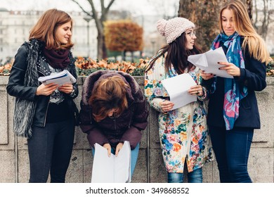 Happy girls checking the results in the park after the exam