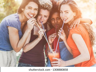 Happy girls drinking cocktail in summer party outdoor - Young women having fun together at music festival - Friendship, youth and vacation concept - Focus on right female face