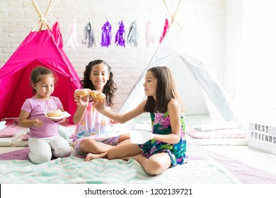 Happy girls enjoying fresh donuts while sitting against teepee tents at home