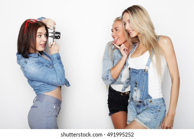 Happy girls friends taking some pictures with camera