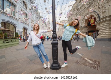 Happy girls friends travelers having fun at the Arbat Street in Moscow