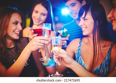 Happy girls and guys toasting at party