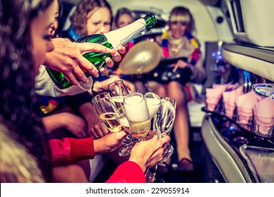 Happy girls having fun in limo, drinking champagne, hen-party