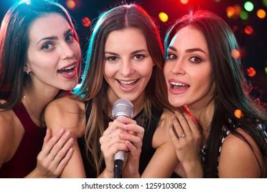 Happy girls having fun singing at a party