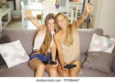 Happy girls at home playing with console sitting on sofa