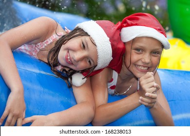 happy girls in inflatable pool wearing christmas hats