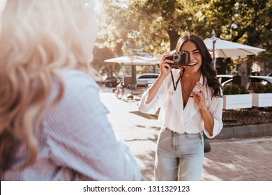 Happy girls making outdoor photoshoot. Brunette female photographer with camera taking pictures of friend.