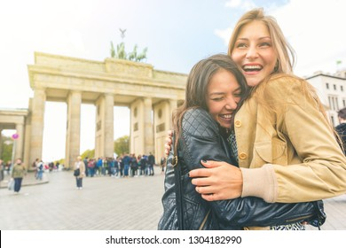 Happy girls meeting and embracing in Berlin. Two young women sharing happiness and love with Brandenburg Gate on background. Happiness, lifestyle and tourism concepts