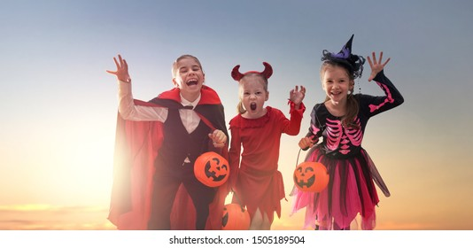 Happy girls on Halloween. Funny kids in carnival costumes outdoors. Cheerful children and pumpkins on sunset background.