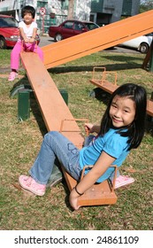 Happy girls playing seesaw at the playground in the park on sunny day