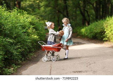 Happy girls roll a stroller with a doll. Children play in the park on a summer day. Childhood and motherhood