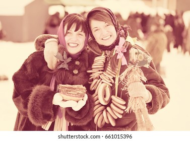Happy girls in russian traditional clothes with pancake and round cracknel during  Shrovetide