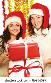 Happy girls in santa hats giving xmas presents isolated on white background