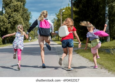 Happy girls with school bags run and jump