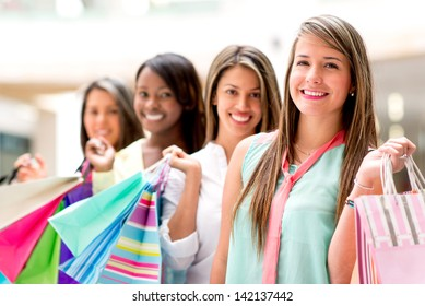 Happy girls shopping at the mall and holding bags