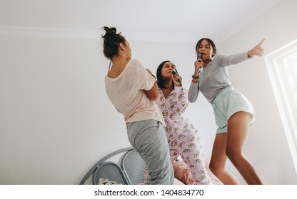 Happy girls singing and dancing on bed during a sleepover at home. Young girls having fun singing in karaoke style  standing on bed holding hair brush.