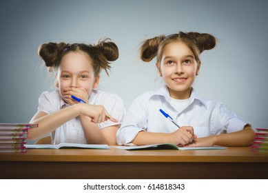 Happy girls sitting at desk on gray background. school concept