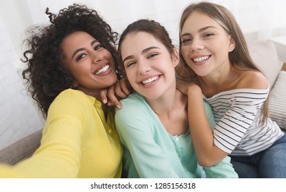 Happy girls taking selfie, having fun and enjoing their time together at home