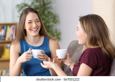 Happy girls talking and laughing and holding coffee cups sitting on a sofa in the living room at home
