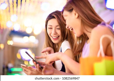 happy girls using smart phone in the shopping mall