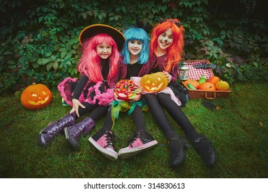 Happy girls in wigs and Halloween costumes holding pumpkins and sweets
