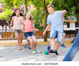 Happy glad  cheerful positive smiling children  playfully running after ball outdoors in park