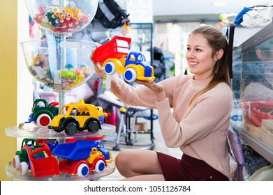 Happy glad positive smiling woman buyer choosing toys for baby in the shop of toys for children