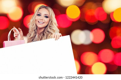 Happy glamorous woman fashion model with shopping bag and empty paper singboard on celebration bokeh background