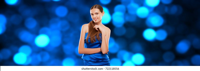 Happy Glamorous Young Woman Wearing a Blue Stylish Dress in a Club at a Disco, space Blue Background and Twinkling Lights