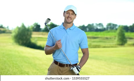 Happy golf player with club smiling on camera, luxury hobby and sport, activity