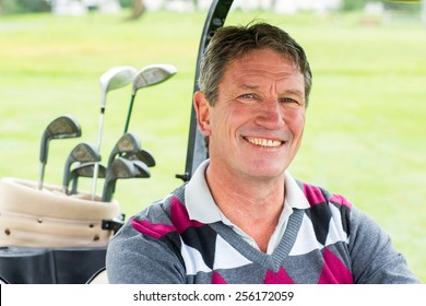 Happy golfer driving his golf buggy smiling at camera on a sunny day at the golf course