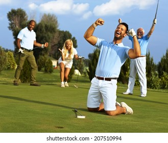 Happy golfer kneeling at hole with raised fists after putting in golf ball to the hole.