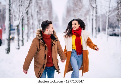 Happy and good day with beloved. Excited young couple in love are walking together in winter city park and have a fun