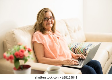 Happy good looking Hispanic lady sending an email holding her computer on her lap and sitting in the living room
