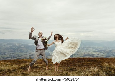 happy gorgeous bride and stylish groom jumping and having fun, boho wedding couple, luxury ceremony at mountains with amazing view, space for text
