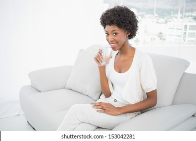 Happy gorgeous brunette drinking water sitting on cosy sofa