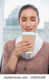Happy gorgeous businesswoman in bright office smelling coffee