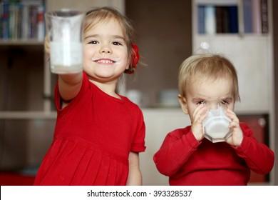 Chúc mừng cô bé tuyệt đẹp với bộ ria mép sữa cho thấy một ly rỗng trong khi anh trai nhỏ dễ thương của cô uống một ly sữa ở nhà, khái niệm thực phẩm và đồ uống, thực phẩm lành mạnh, trong nhà