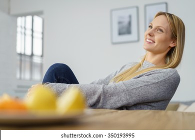 Happy gorgeous young woman sitting daydreaming at home looking up into the air with a faraway expression and smile of pleasure, low angle view over the dining table and fresh fruit