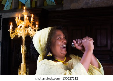 Happy gospel singer with microphone singing during mass